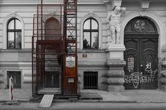 Alte Schwarzweiss-Wand mit dem modernen roten Aufzug im Bau stockfotografie