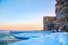 Alte scogliere nel mare, tutte in ghiaccio Rupe al tramonto nel ghiaccio un bello paesaggio dal Sun uscente Fotografia Stock