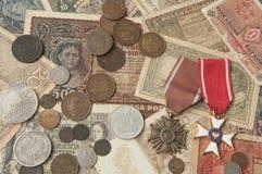Alte Silber- und Kupfermünzen mit Banknoten und Medaillenhintergrund Lizenzfreies Stockfoto