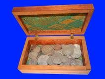 Alte Silbermünzen in einem Kasten auf einem blauen Hintergrund Stockfotografie