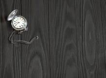 Alte silberne Taschenuhr, die auf einem Holztisch liegt Stockfotografie