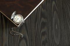 Alte silberne Taschenuhr und ein Buch Lizenzfreie Stockfotos