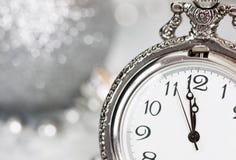 Alte silberne Uhr nah an Mitternacht und Weihnachtsdekorationen Lizenzfreie Stockfotos