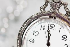 Alte silberne Uhr nah an Mitternacht und Weihnachtsdekorationen Lizenzfreies Stockfoto