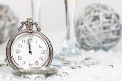 Alte silberne Uhr nah an Mitternacht und Weihnachtsdekorationen stockbilder