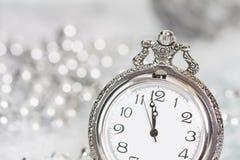 Alte silberne Uhr nah an Mitternacht und Weihnachtsdekorationen Lizenzfreies Stockbild