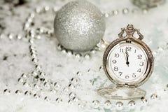 Alte silberne Uhr nah an Mitternacht und Weihnachtsdekorationen Stockfotografie