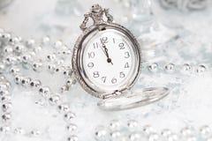 Alte silberne Uhr nah an Mitternacht und Weihnachtsdekorationen Lizenzfreie Stockfotografie
