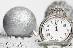 Alte silberne Uhr nah an Mitternacht und Weihnachtsdekorationen lizenzfreie stockbilder