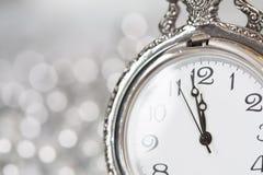 Alte silberne Uhr nah an Mitternacht und Weihnachtsdekorationen Stockbild