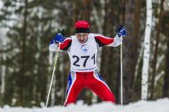 Alte Skifahrerathletenmänner, die durch Holz laufen Stockbild