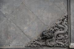 Alte Skulptur eines Drachen auf Steinwand Stockbild