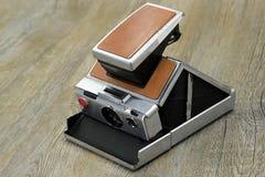 Alte sofortige Kamera auf Holzfußboden Lizenzfreie Stockfotos