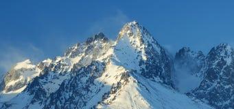 Alte sommità nevicate sotto cielo blu Immagini Stock Libere da Diritti