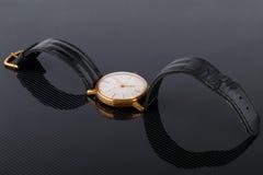Alte sowjetische Armbanduhr auf schwarzem glattem Hintergrund Stockbilder