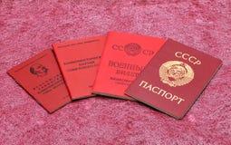 Alte sowjetische Dokumente auf einem roten Hintergrund Stockfotos