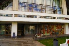 Alte sowjetische Hotelfassade mit Steinsäulen, panoramische Fenster, schräges Dach, setzen auf dem grasartigen Rasen neben dem Ei Lizenzfreies Stockfoto