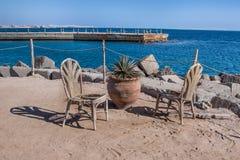 Alte St?hle des Weidenrattans auf dem Strand der Hintergrund des Meeres und des Piers stockfoto