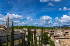 Alte Stadtansicht Gironas mit grünen Bergen und blauem Himmel mit Wolken Lizenzfreies Stockfoto