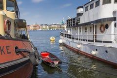 Alte Stadtgebäude und alte Boote auf Wasser unter blauem Himmel in Stoc Stockfotografie