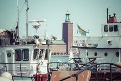 Alte Stadtgebäude und alte Boote auf Wasser unter blauem Himmel in Stoc Lizenzfreies Stockfoto