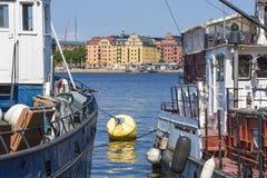 Alte Stadtgebäude und alte Boote auf Wasser unter blauem Himmel in Stoc Lizenzfreie Stockfotos