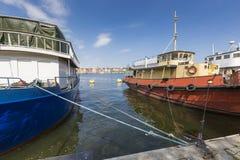 Alte Stadtgebäude und alte Boote auf Wasser unter blauem Himmel in Stoc Stockbilder