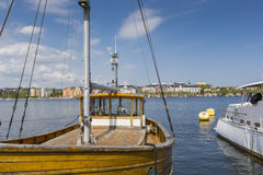 Alte Stadtgebäude und alte Boote auf Wasser unter blauem Himmel in Stoc Stockbild