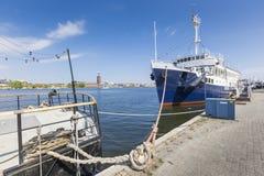Alte Stadtgebäude und alte Boote auf Wasser unter blauem Himmel in Stoc Lizenzfreie Stockfotografie