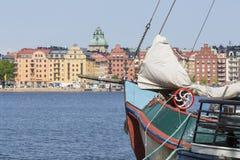 Alte Stadtgebäude und alte Boote auf Wasser unter blauem Himmel in Stoc Lizenzfreie Stockbilder