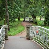 Alte Stahlbrücke mit Metallgeländern im Palastpark Lizenzfreies Stockfoto