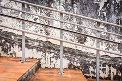 Alte Stahlgeländerdocken und alte Zementwand Stockfotografie
