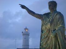 Alte Statue des Kaisers Nero mit in Abstand die Extremität eines Leuchtturmes zum Sonnenuntergang in der Stadt von Anzio in Itali Stockfoto