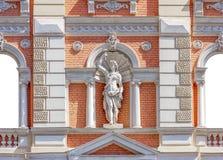 Alte Statue eines Heiligen auf einer orange Backsteinmauer Lizenzfreies Stockbild