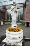 Alte Statue mit Blumen Lizenzfreie Stockfotografie