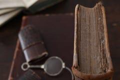 Alte staubige Bücher mit Lesebrille Stockbilder