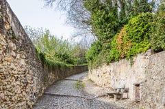 Alte Stein-Straße in der Italiener ummauerten Stadt von Soave mit Steinbank Lizenzfreie Stockfotografie