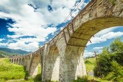 Alte Steinbrücke auf einem Hintergrund des blauen Himmels Stockfoto