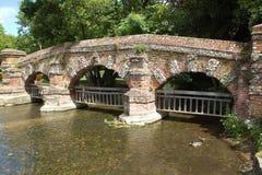 Alte Steinbrücke und Viehzaun auf Fluss in Kent, England Lizenzfreies Stockbild