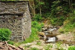 Alte Steinhaus- und Wasserstromwasserfälle Stockfoto