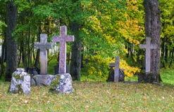 Alte Steinkreuze auf Gräbern mit Herbst Stockfotos