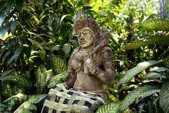 Alte Steinstatue einer alten Gottheit auf der Insel von Bali in einem tropischen Wald unter den Bäumen an einem sonnigen Tag Stockbilder