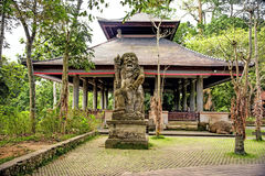 Alte Steinstatue einer alten Gottheit auf der Insel von Bali in einem tropischen Wald unter den Bäumen im Hintergrund von Lizenzfreies Stockfoto