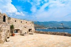 Alte Steinwände der mittelalterlichen Festung Eine Seebucht mit malerischen Bergen veranschaulichung stockfotos