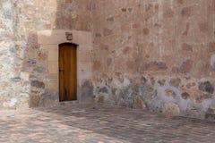 Alte Steinwände und Holztür Stockfotografie