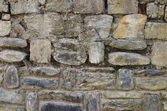 Alte alte Steinwand hergestellt von den Flusssteinen der Wildform, befestigt mit Lehm-, Beige und Gelblicherhintergrundbeschaffen Stockfotografie