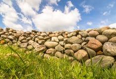 Alte Steinwand mit grünem Gras im vorderen und blauen Himmel mit Wolken oben Stockfotos