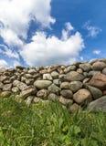 Alte Steinwand mit grünem Gras im vorderen und blauen Himmel mit Wolken oben, vertikales Bild Lizenzfreie Stockfotos