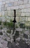 Alte Steinwand mit Pfeil-Schlitz Stockbild