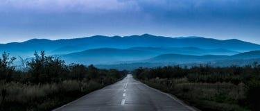 Alte Straße, die zu die blauen Hügel führt Lizenzfreie Stockfotos